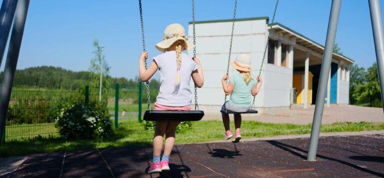 Kaksi tyttöä keinuu aurinkoisella säällä.