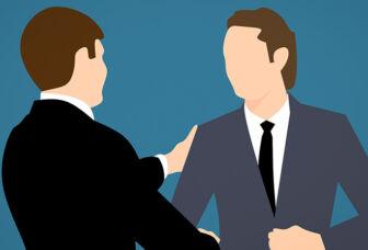 Kaksi tummaan pukuun pukeutunutta miestä kättelee, piirroskuva.