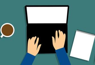 Henkilö kirjoittaa tietokoneella, vieressään kahvikuppi ja muistiinpanovälineet.