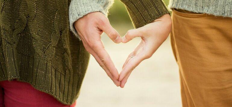 Rakastuneet muodostavat käsillän sydämen yhdessä.