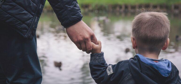 Aikuinen pitää lasta kädestä kiinni ja he katselevat yhdessä sorsia.