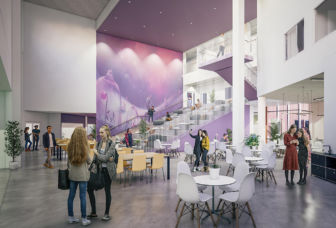 Pöytäryhmiä Turengin koulukeskuksen aulassa ja suuret portaat seuraavaan kerrokseen.