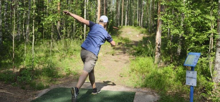 ReTee ry:n talkoileman frisbeegolfradan avajaisissa henkilö heittämässä frisbeetä.
