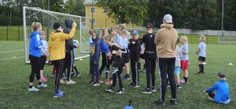 SC Urbansin kesäleirillä lapset ja ohjaajat jalkapallokentällä kerääntyneenä maalin taakse.