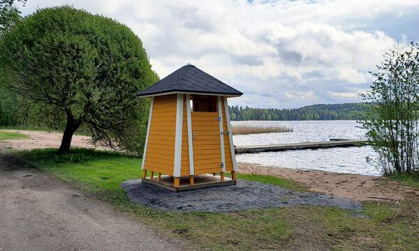 Tietyn uimarannan keltainen pukukoppi sekä pitkä laituri.