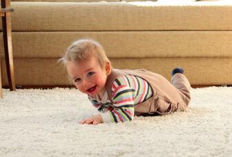 Puolivuotias vauva ryömii olohuoneen lattialla.