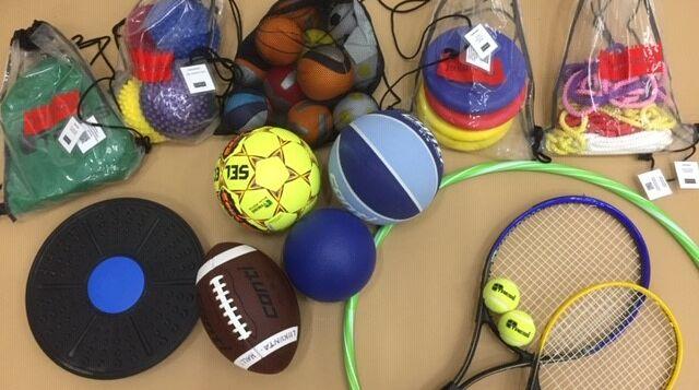 Liikuntavälinelainaamon välineitä, mm. tasapainolauta, amerikkalainen jalkapallon, tennismailat ja hulavanne.